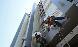 Workers washing the windows facade of a modern office building.